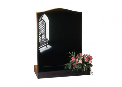 Black granite headstone with etched and painted 'church window and bible' design